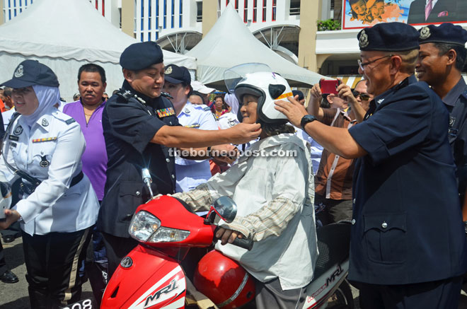 Mazlan (third left) helps a motorcyclist to buckle up her helmet as Koo (right) looks on.