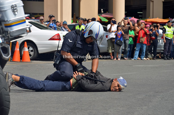 A policeman pinning down an 'armed robbery suspect' during the launch of 'Ops Selamat'.