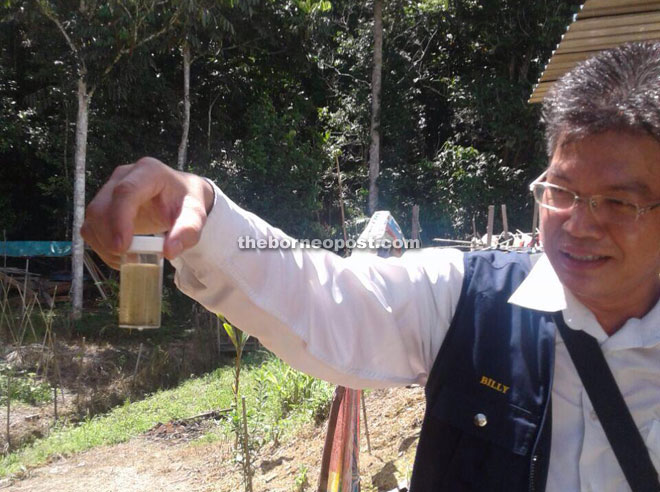 The head of Sarawak Health Department vector borne diseases control unit Billy Sujang shows a sample containing mosquito larvae during a recent campaign at a longhouse in Kapit.