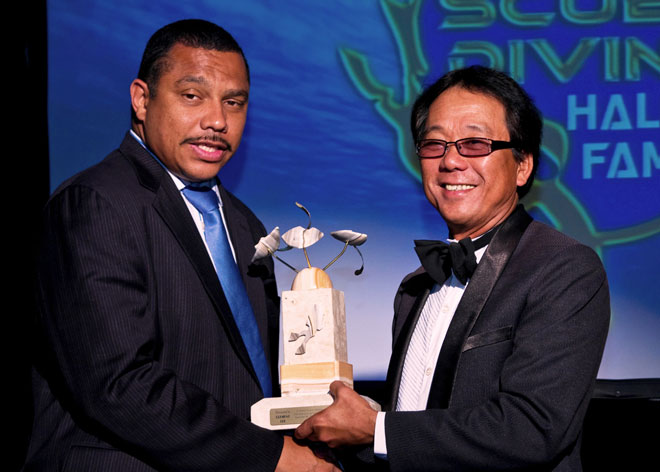Clement Lee (right) receives the ISDHF Award from Cayman Island director of tourism.