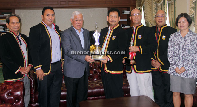 Ik Pahon (fourth right) receives the Dato Sri Michael Manyin Challenge Trophy from Manyin, as other committee members of the golf tournament look on.