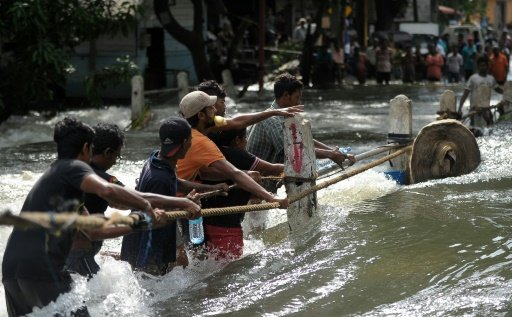 Sri Lankans cross a torrent of floodwaters in Kelaniya, on the outskirts of Colombo on May 21, 2016. Photo by AFP