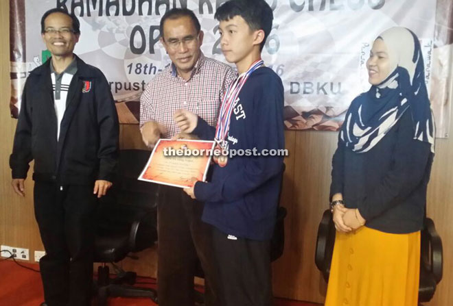Len (second left) presents a certificate to a young player who recently did well in a national tournament. On his right is Reduan.