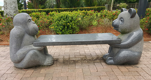 A stone bench resting on the palms of two statues —  an orangutan and a panda.