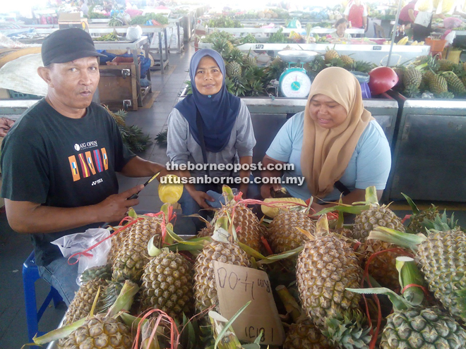 (From left) Ahmad, Azinah and her sister Hasinah Abu Bakar at their pineapple stall at Sarikei Wet Market.