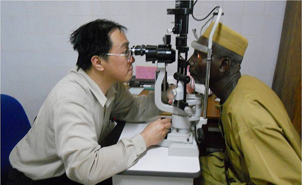 Photo of Dr Lim  checking the eyes of a patient (picture bottom) in Africa during a one-month stint in Africa in 2012. — Photos courtesy of Prof Dr Lim Lik Thai