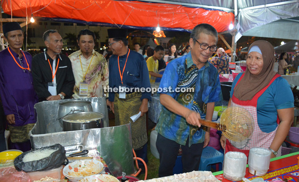 Dr Annuar (second from right) trying his skills in cooking at a stall in Sibu Town Square Phase 1.