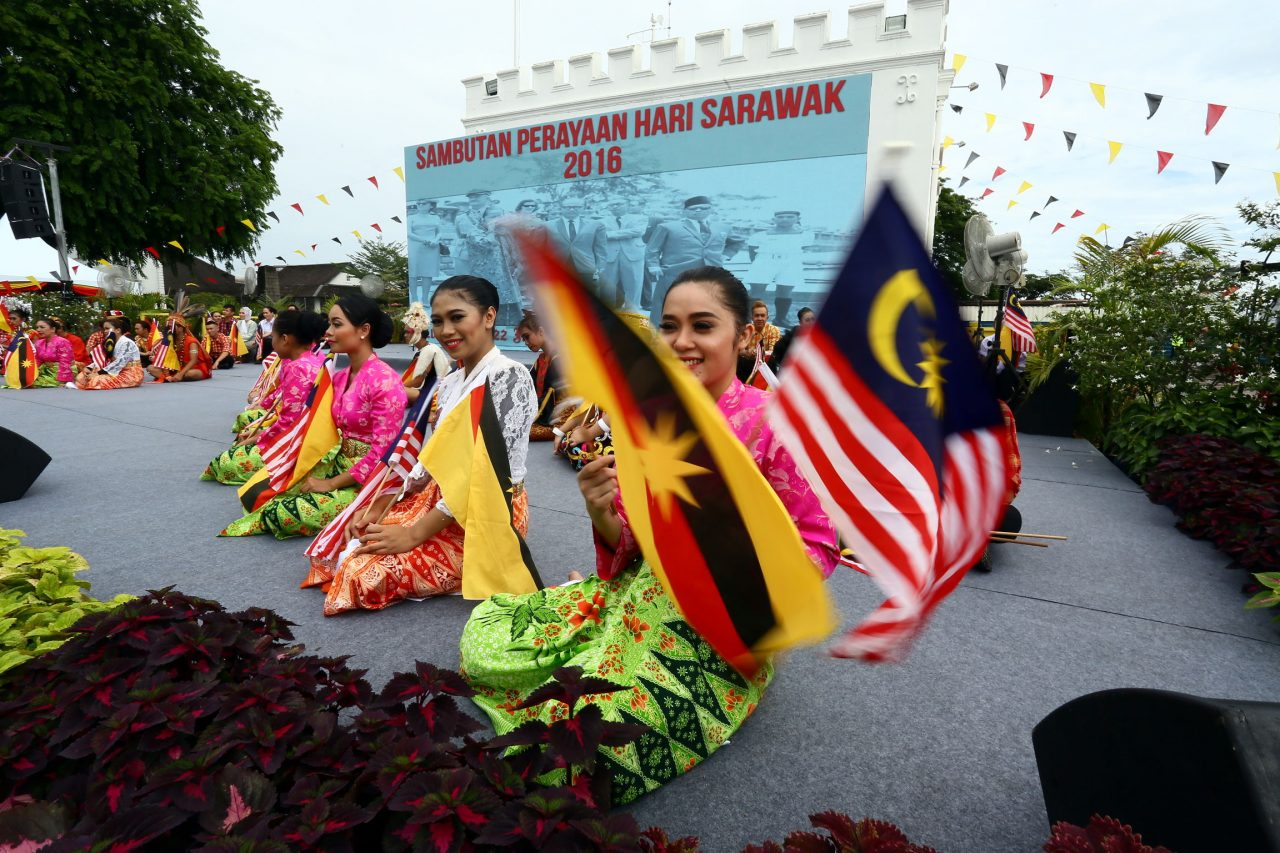 One of the performers during the Sarawak Day celebrations waves both the flag of Sarawak and the Jalur Gemilang.