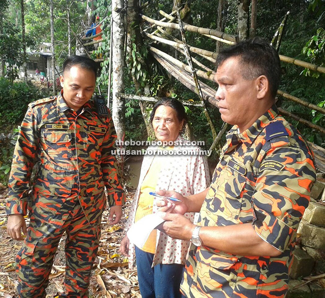BANTUAN: Mangsa (tengah) diberi bantuan oleh pihak bomba sebelum dihantar ke Hospital Serian untuk pemeriksaan.