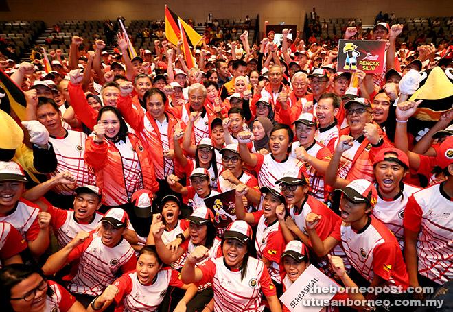 SELAMAT BERJUANG!: Adenan, Jamilah dan tetamu jemputan bersama atlet SUKMA Sarawak melaungkan kata-kata semangat selepas majlis penyerahan bendera Sarawak di UNIMAS, semalam.