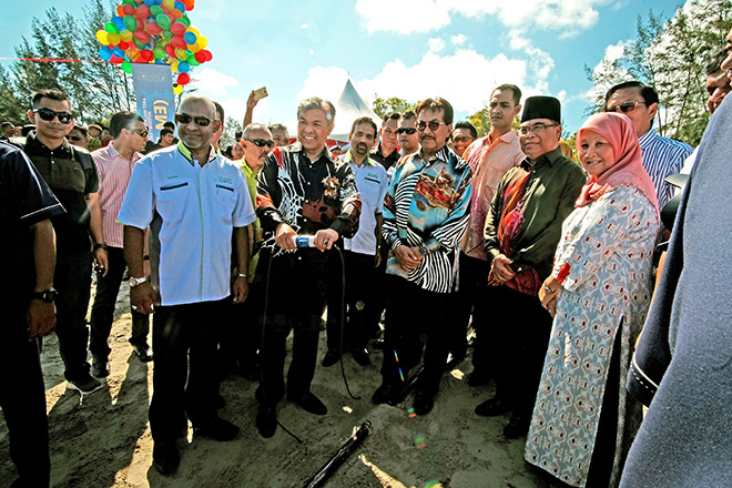 Ahmad Zahid (holding a button) performing the ground-breaking ceremony of the EM-IIG project by pressing the button to mark the launching ceremony at Suang Lumut village in Rampayan Laut, Kota Belud, yesterday.