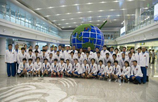 Members of North Korea's delegation for the 2016 Rio de Janeiro Olympic Games, pictured on July 26, 2016, pose for a group photo before leaving Pyongyang International Airport for Brazil