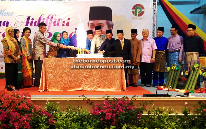 Awang Tengah (eighth right), flanked by Asfia (on his right) and Sarudu, together with Naroden (sixth right) and other guests cut the Hari Raya cake during the open house.