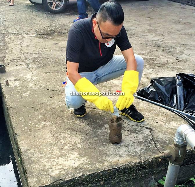 A Dengue Warrior taking part in the 'Spot, Tag and Clean' initiative to identify dengue breading ground in public areas.