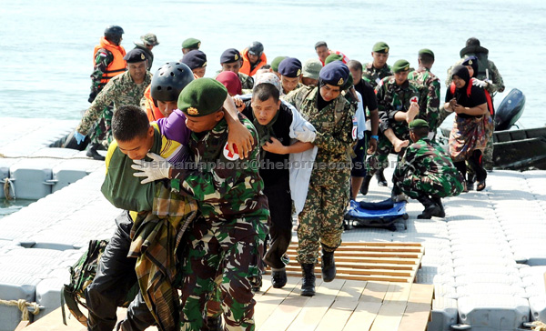 Malaysian Armed Forces personnel and their Indonesian counterparts carrying 51 'flood victims' to a safer place during the joint exercise. — Bernama photo
