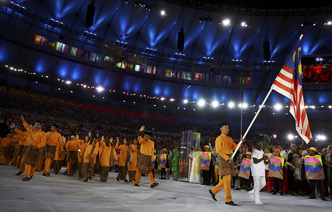Flagbearer Datuk Lee Chong Wei leads the Malaysian contingent into the stadium. (Inset) Fireworks explode during the curtain-raiser. — Reuters photo