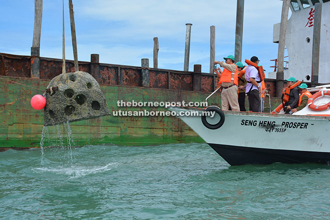 Jaul takes a photo as an artificial reef ball is deployed at the Miri-Sibuti Coral Reef Complex.