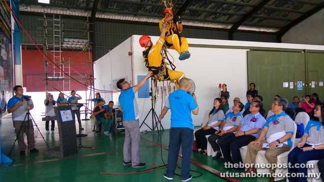 (From second right) Nelson, Lee and others watch a rope access training (RAT) demonstration at Oceancare's Rope Access Training Centre in Piasau.