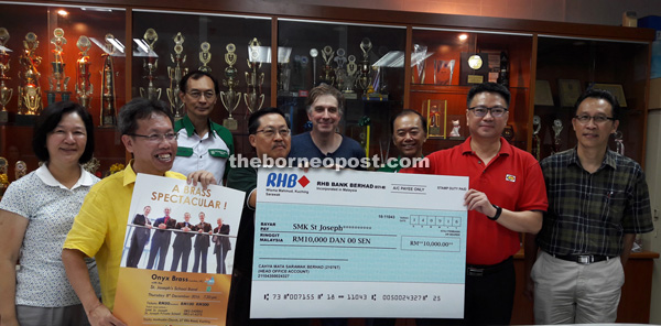 Ling (second right) hands over the cheque to Lau. From left are June and Dr Sim as well as committee members. Jonathan is on second left, back row.