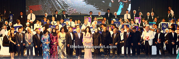 Guests-of-honour and special guests pose with performers (in the background). — Photo by Muhammad Rais Sanusi