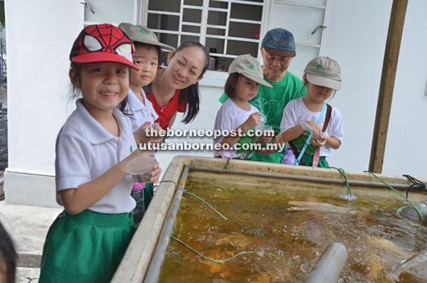 Children feeding freshwater fish while learning about aquaponics.