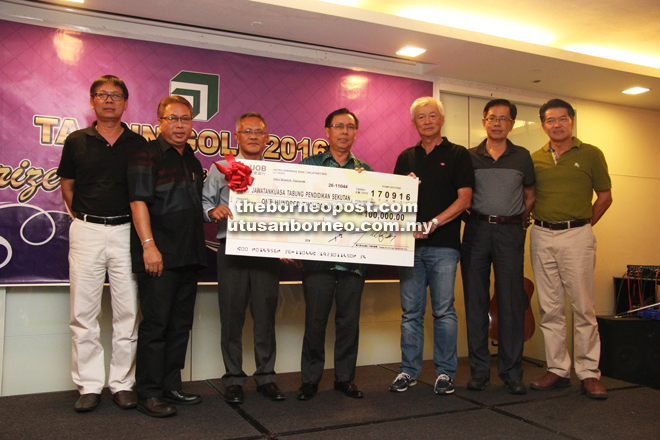 Meikle (left) receives a mock cheque from Wong while  Dr Rundi (centre) and others look on.
