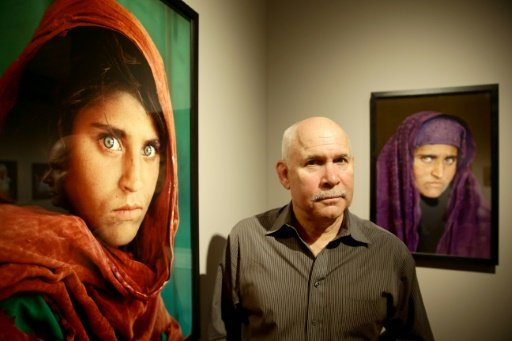 """US photographer Steve McCurry poses next to his photos of the """"Afghan Girl"""" named Sharbat Gula at a 2013 exhibition in Hamburg, northern Germany. - DPA/AFP/Lehaz Ali"""