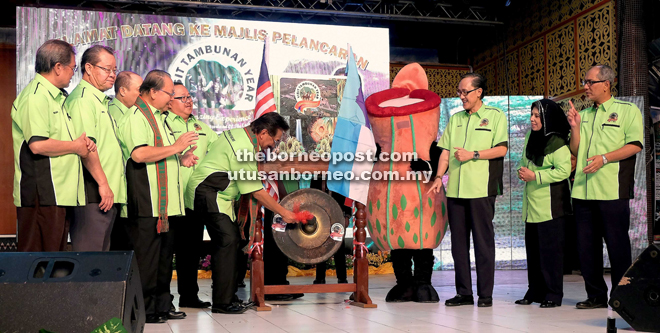 Musa striking the gong seven times to launch the Visit Tambunan Year 2017, watched by Pairin and others.