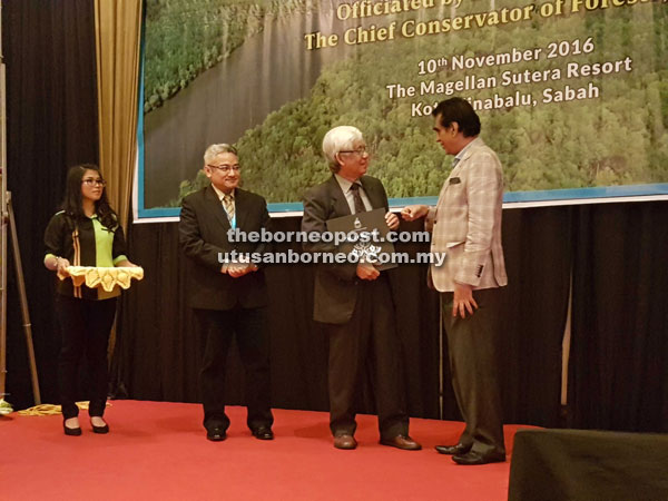 Sam (right) presenting a memento to Dr J. E. Ong, an expert on mangroves and wetlands at the launch of the second Sabah Ramsar Conference 2016 yesterday.