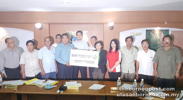 Chong (fifth right) presents the mock cheque to Bronnie.
