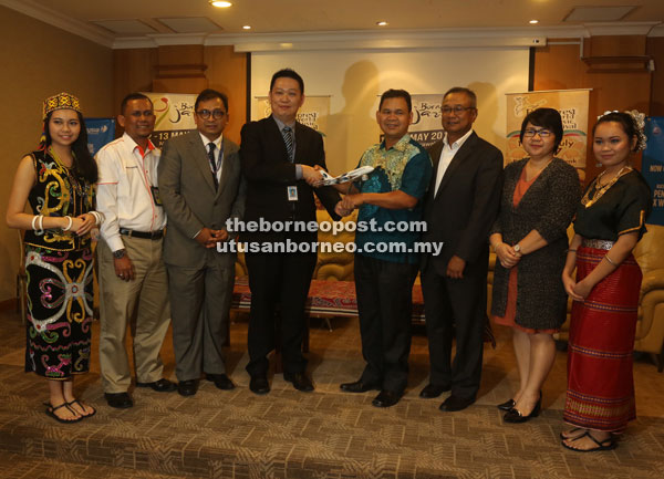 Kong (fourth left) presents a memento to Ik Pahon, witnessed by (from second left) Mohd Nadzim, Alias, Ibrahim and Mary. — Photo by Jefferey Mostapa