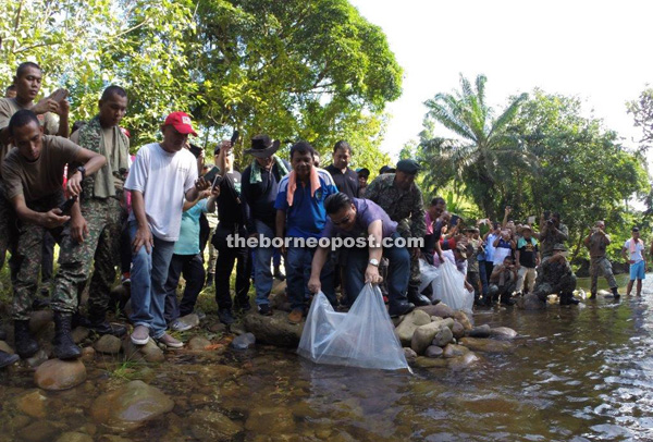 Miro, accompanied by volunteers, releasing the fish fry into the river.