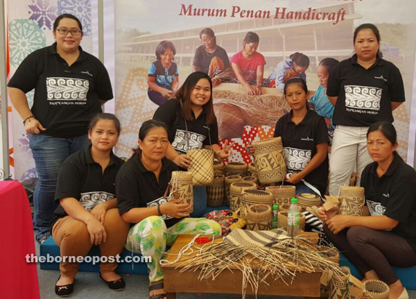 The artisans proudly showcase their products. Also in the picture are Sarawak Energy Community Relations assistant Florida Havit (left, back row) and Community Relations executive Alis Ekan (second left, back row).