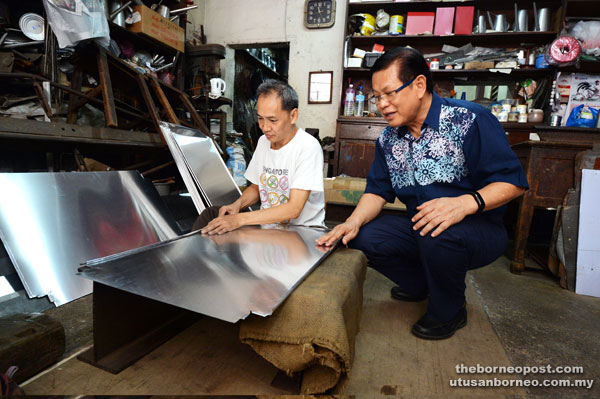 Lee (right) visiting a tinsmith during the Kuching Heritage Walk yesterday.