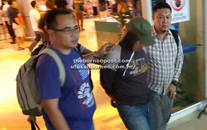 SIASATAN LANJUT: Pegawai imigresen yang ditahan di Kuantan, Pahang diiringi pegawai JSJ Sarawak tiba di Lapangan Terbang Antarabangsa Kuching untuk siasatan lanjut.