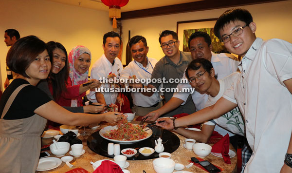 Khoo (fourth left) joins the hotel staff, media personnel and other invited guests in tossing Yee Sang.