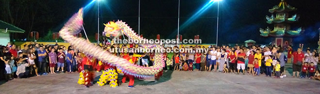 Visitors enchanted by a dragon dance performance.