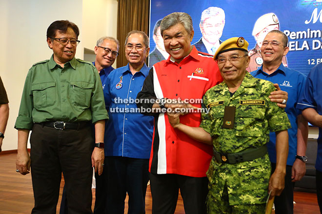 Zahid (third right) pointing at the service recognition badge he pinned on one of the Rela members while (from left) Abang Johari, Riot, Wan Junaidi and Fadillah look on. — Photos by Muhammad Rais Sanusi