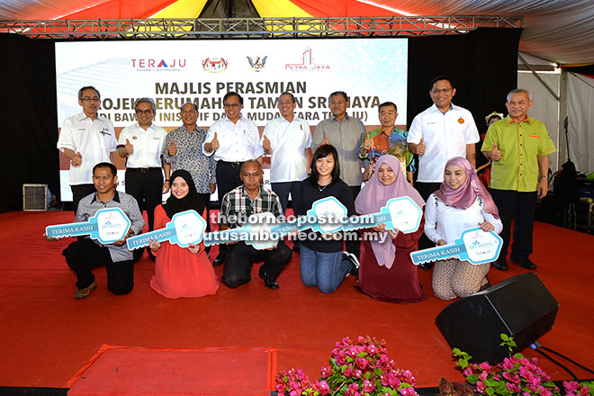 Abang Johari (back row, fourth left) together with Fadillah (back row, centre), Morshidi (back row, fourth right), Naroden (back row, third right), Talib (back row, right), Dr Abdul Rahman (back row, second right), Hamid (back row, third left) and others giving the thumbs-up during a group photo with new Taman Sri Maya house owners. — Photo by Tan Song Wei