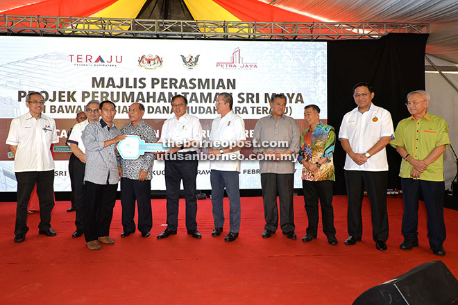 Abang Johari (sixth right) presenting a replica key to one of the new Taman Sri Maya house owners while (from right) Talib, Dr Abdul Rahman, Naroden, Morshidi, Fadillah, Hamid and Husni look on. - Photo by Tan Song Wei