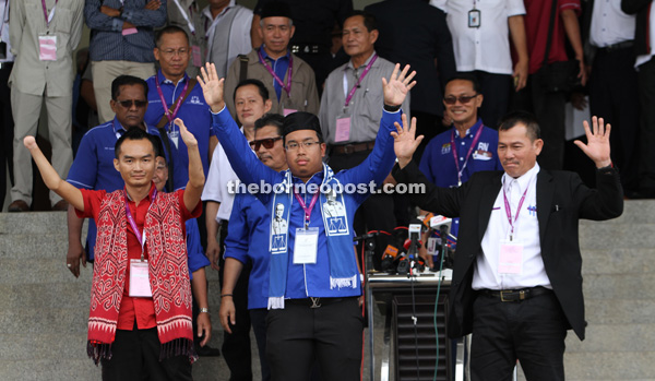 Azizul (centre) raises his hands upon the announcement of his mother's candidacy. At right is Rapelson and at left, Anthony.