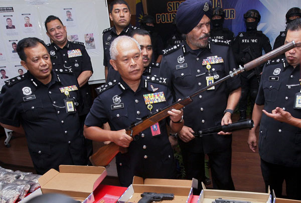 Mohmad Salleh (second left) shows a confiscated rifle at the press conference. — Bernama photo