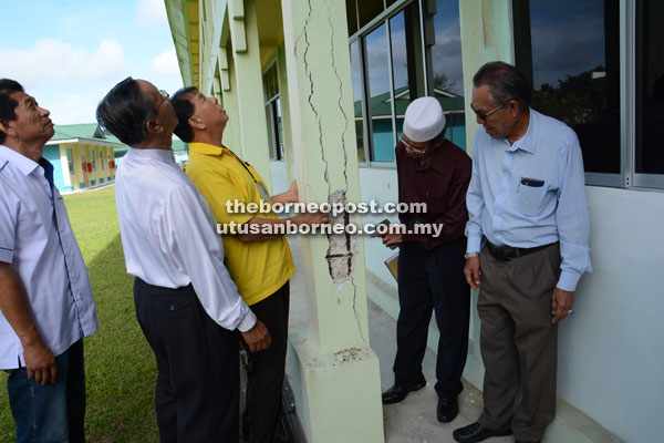 Ting (third left) inspects one of the building's pillars that has cracks on it – a large chip on the side exposes the steel rods inside the pillar.