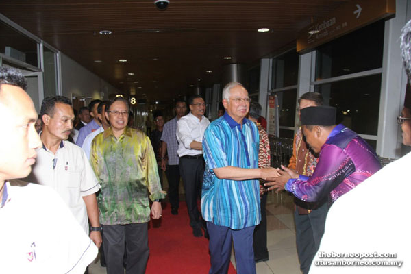 Najib (right) and Hishammuddin (behind Najib) being greeted by community leaders upon their arrival. Also with them is Abang Johari (third left). — Photo by Chimon Upon