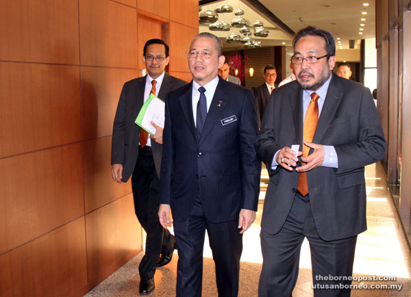 Fadillah, accompanied by Mohd Radzif (right), making his way to the ballroom for SME Bank's Pan Borneo Market Outreach Programme at a hotel in Kuching yesterday. — Photo by Chimon Upon