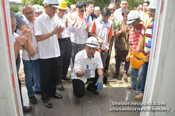 Jailani gives the thumbs-up after placing a tile to symbolically launch the new site of 1Malaysia Internet Centre in Kpg Tanah Hitam.