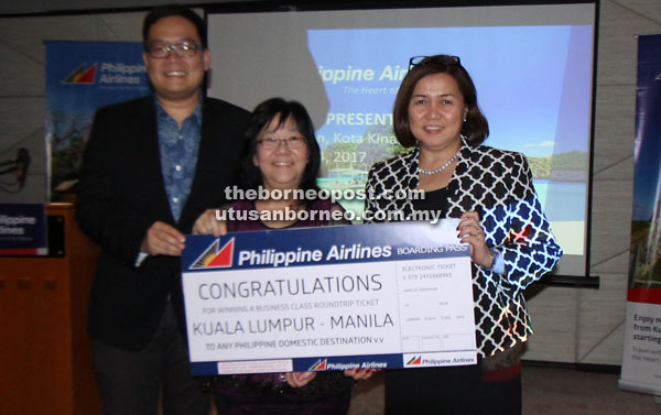 One of the lucky winners receiving the air ticket to Manila from Ryan.