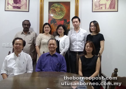 Tan (seated left) and Ngeng (seated, centre) pose for a group photo after the press conference.
