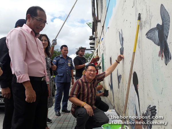 Wee (squatting) admiring a mural while Jumaini (left) and others look on.