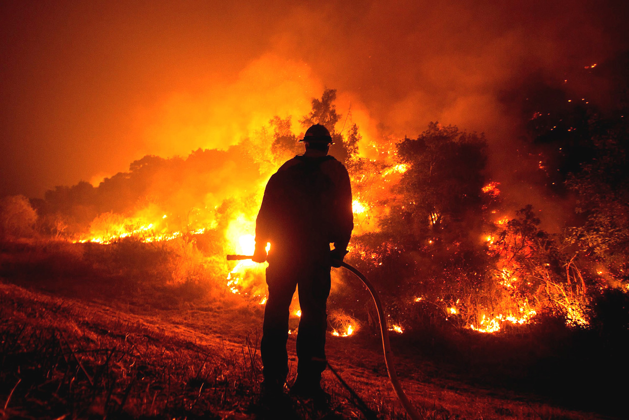 A firefighter watches the Bobcat Fire burning on hillsides near Monrovia Canyon Park in Monrovia California. — AFP